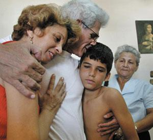 BACK HOME: Released Cuban dissident Manuel Vazquez Portal reunites with his son Gabriel, wife Yolanda, left, and sister Francisca in Havana on Thursday. ADALBERTO ROQUE/AFP-GETTY IMAGES